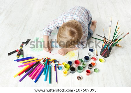 Child drawing picture with crayon  in album using a lot of painting tools. Creativity concept. - stock photo