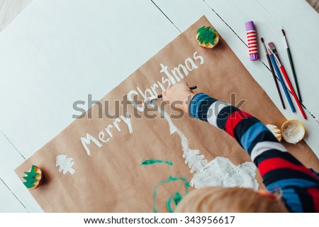 Child drawing the Christmas message, Merry Christmas - stock photo