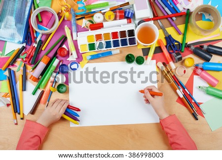 Child drawing top view. Artwork workplace with creative accessories. Flat lay art tools for painting. - stock photo