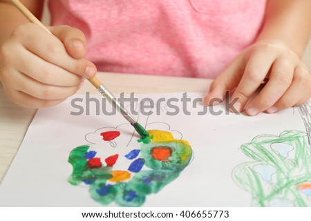 Child drawing tree with bright paints on paper, closeup - stock photo