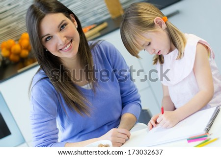 Child drawing with crayons with her mom, sitting at table in kitchen at home - stock photo