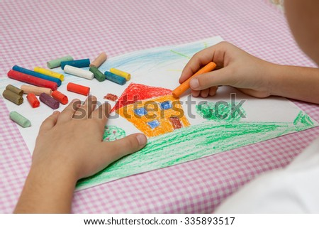 Child draws a pencil drawing of the peace. Green field, the bushes and the house. - stock photo