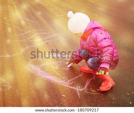 Child draws with chalk on the playground. - stock photo
