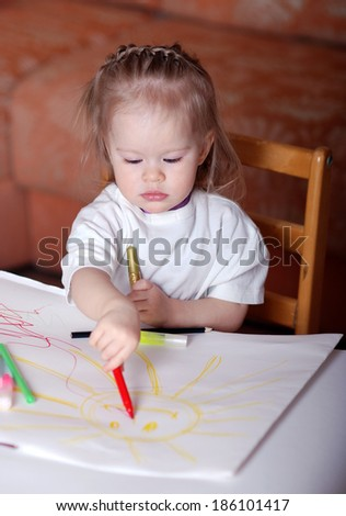 child draws with crayons - stock photo