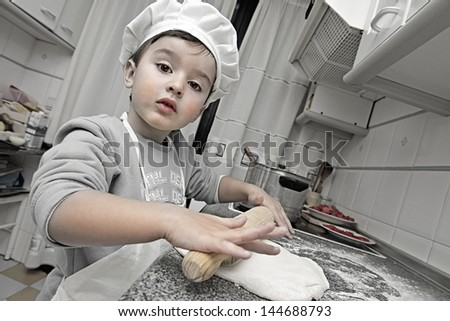 Child dressed as a chef working in the kitchen - stock photo