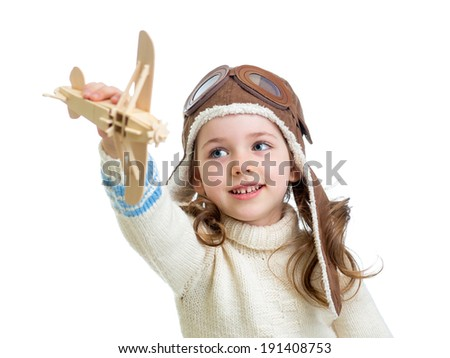 child dressed as pilot and playing with wooden airplane toy isolated on white background - stock photo