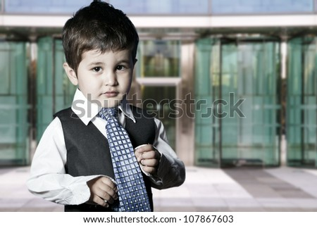 child dressed businessman smiling in front of building - stock photo