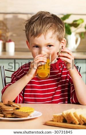 Child drinking orange juice - stock photo