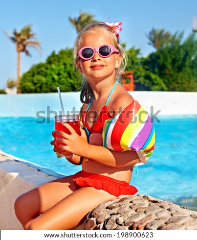 Child drinking soft drink near swimming pool. - stock photo