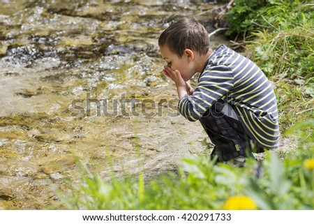Child drinking water from clean mountain river, environmental concept.  - stock photo