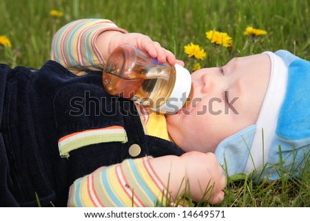 child drinks from a bottle laying in  grass - stock photo