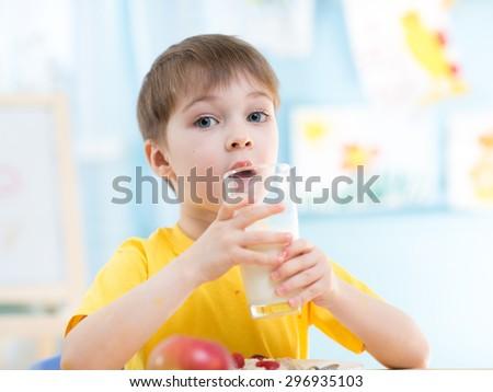 child drinks healthy milk at home or kindergarten - stock photo