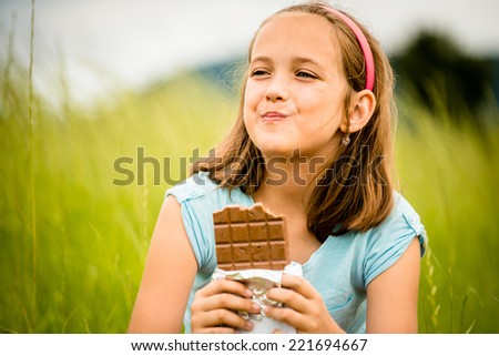 Child eating and relishing chocolate - outdoor in nature - stock photo
