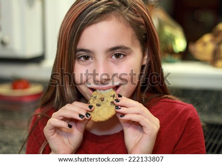 Child eating chocolate chip cookie with milk mustache - stock photo