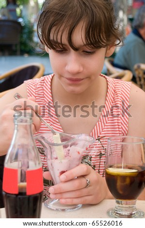 Child eating ice cream with spoon at restaurant - stock photo