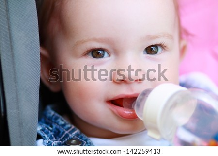 child eating or drinking out of a plastic bottle outdoor - stock photo