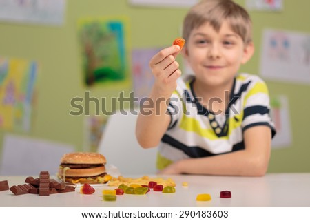 Child eating tasty jelly beans for snacks - stock photo