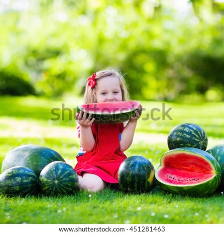 Child eating watermelon in the garden. Kids eat fruit outdoors. Healthy snack for children. Little girl playing in the garden biting a slice of water melon.  - stock photo