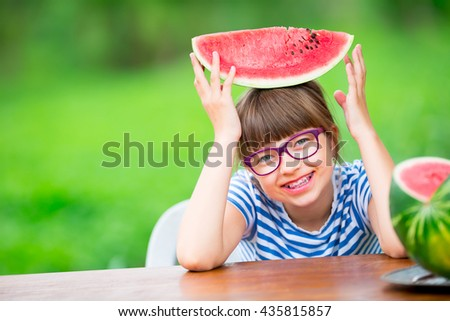 Child eating watermelon. Kids eat fruits in the garden. Pre teen girl with gasses and teeth braces.  - stock photo