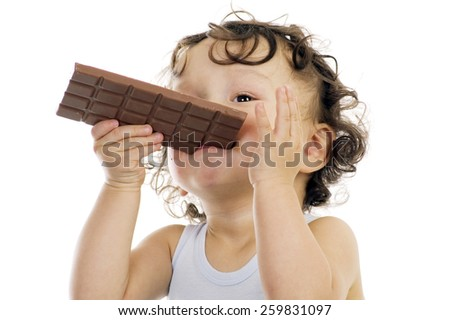 Child eats chocolate,isolated on a white background. - stock photo