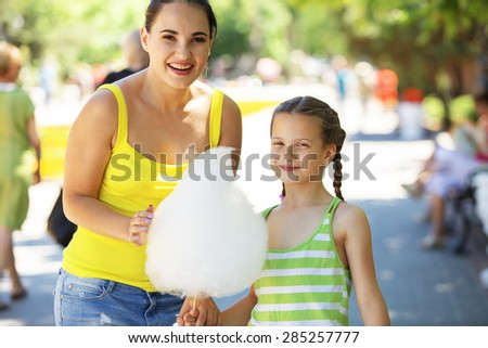 Child eats cotton candy with mom in city street - stock photo