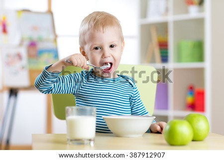 child eats healthy food at home or kindergarten - stock photo