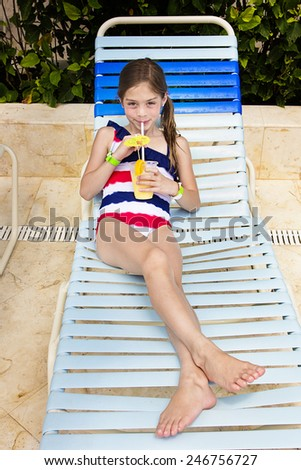 Child enjoying a tropical drink at an outdoor pool - stock photo
