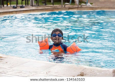 Child Enjoying Swimming in a Pool in Summer - stock photo