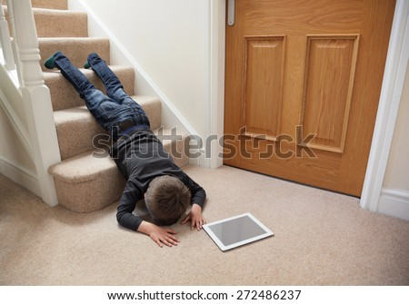 Child falling down the stairs whilst playing on digital tablet not concentrating concept for safety at home - stock photo