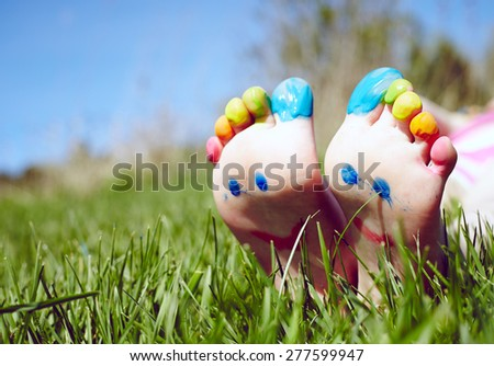 Child feet with painting smiles lying on green grass  - stock photo
