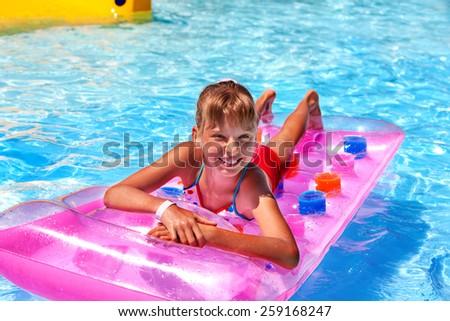 Child female on water slide at aquapark. Summer holiday. - stock photo