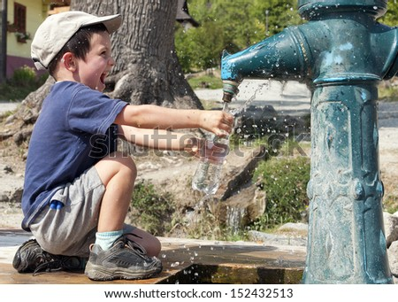 Child filling water bottle from a hydrant fountain.  - stock photo