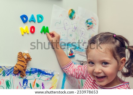 child forming mom and dad words with magnetic letters on refrigerator door. - stock photo