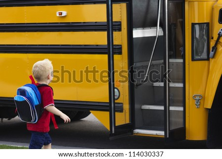 Child getting on a school bus - stock photo