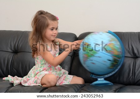 Child (girl age 05) search and examining the Globe  at home. Concept photo travel and education - stock photo