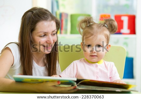 child girl and mother read a book indoors - stock photo