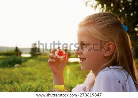 child girl blowing soap bubbles outdoor at sunset - happy carefree childhood - stock photo