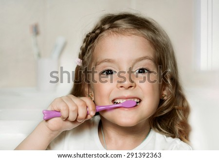 Child girl cleaning teeth with toothbrush in the bathroom. - stock photo