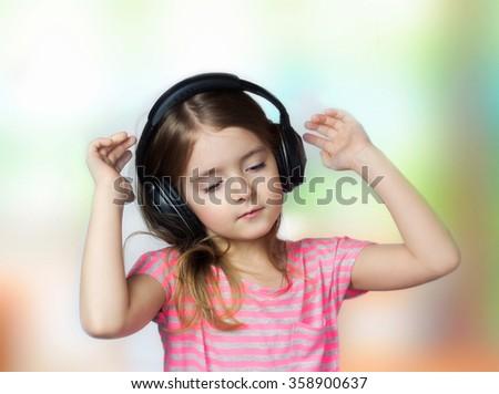 Child girl closed eyes listen music headphones. Kid female earphones mp3 player enjoy. - stock photo