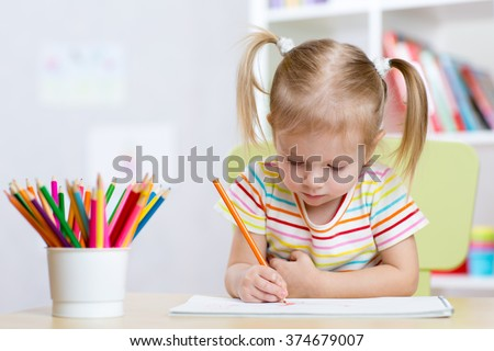 Child girl drawing with colorful pencils in nursery - stock photo
