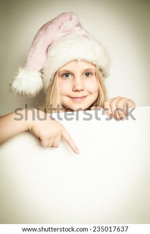 Child girl dressed in Santa Claus hat with paper blank. Christmas concept - stock photo