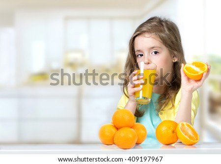 Child girl drinking glass of fresh orange juice indoors.Healthy lifestyle.Kid sitting home at table eating oranges background empty copy space. - stock photo