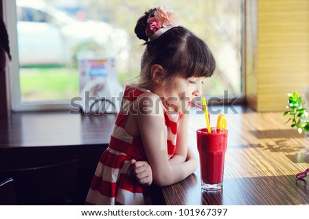Child girl drinking strawberry smoothie sitting at a table in restaurant - stock photo