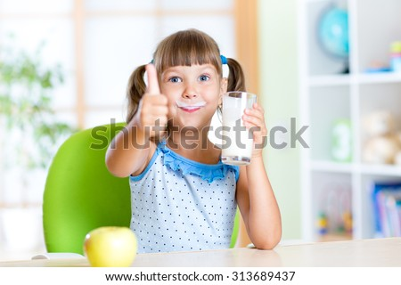 child girl drinks milk and showing thumb up - stock photo
