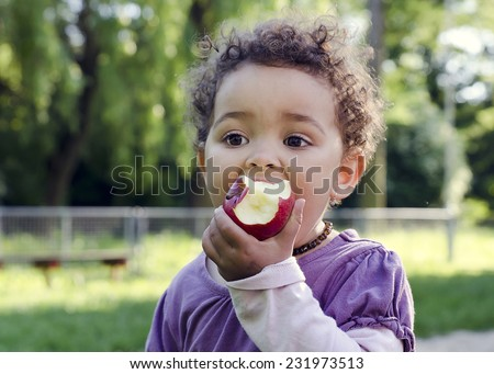 Child girl eating an apple in a park in nature. - stock photo