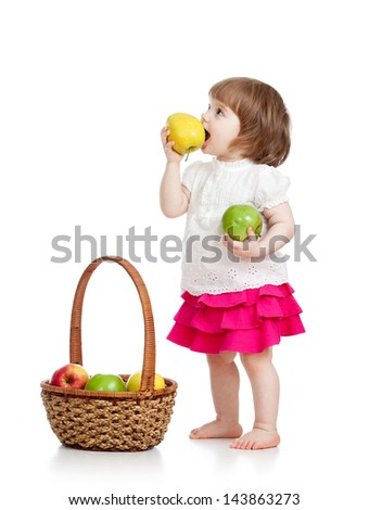 child girl eating apples from basket over white background - stock photo