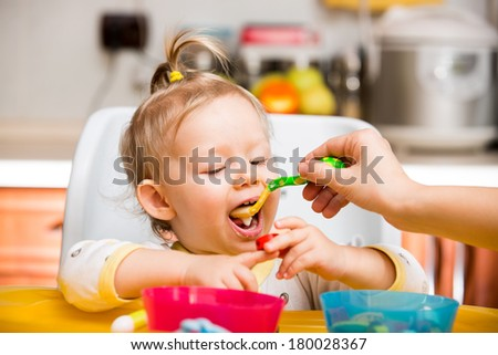Child girl eats porridge from a spoon on kitchen. Use it for child, healthy food concept - stock photo