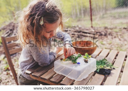 child girl exploring nature in early spring, looking at first sprouts with loupe. Teaching kids to love nature. - stock photo