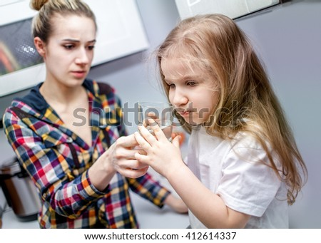 Child girl five years old drinking woter from glass under the supervision of a beautiful young woman - stock photo