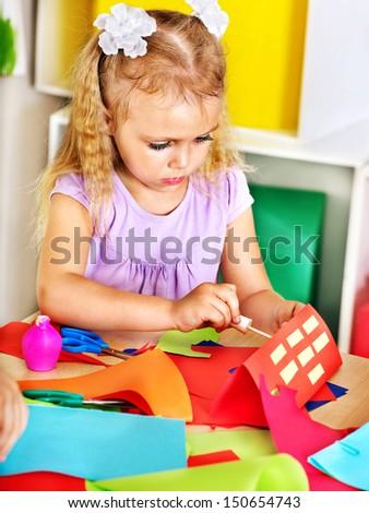 Child girl  glue paper in preschool. - stock photo